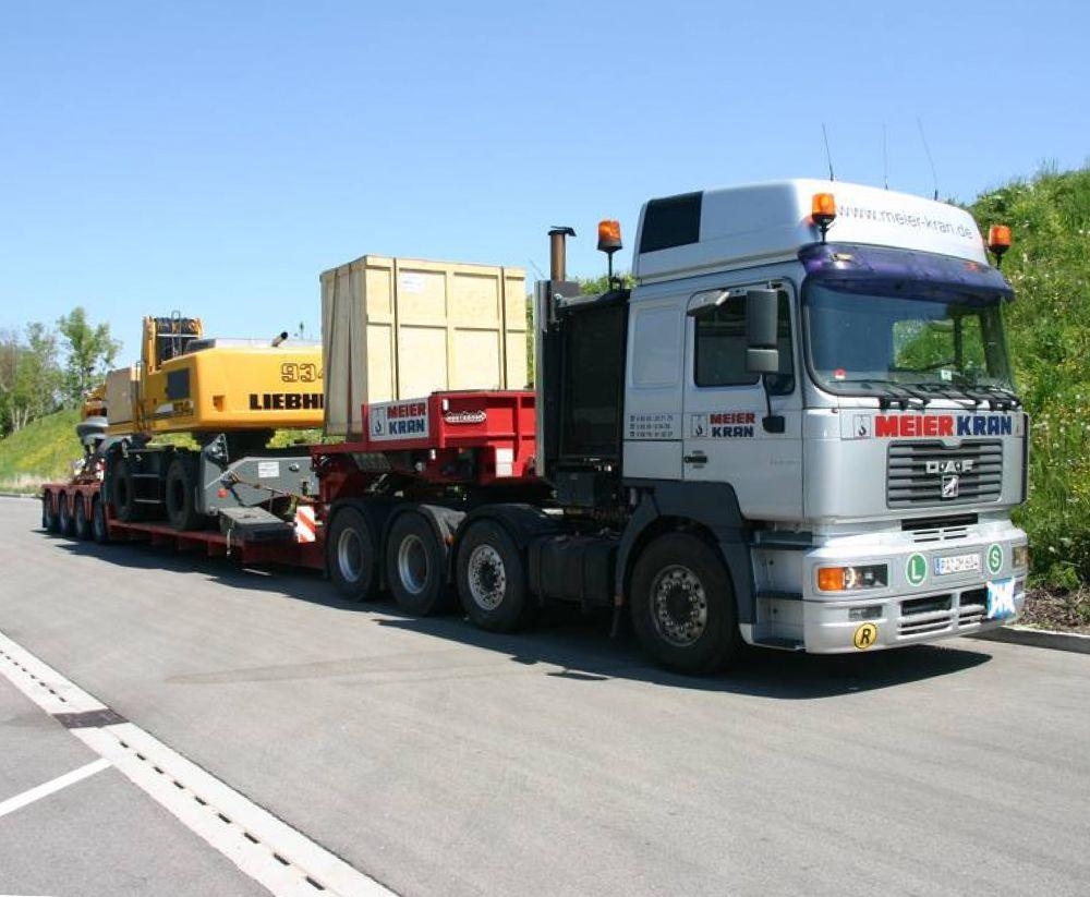 Transport von Baumaschine mit Tieflader und 3-Achs-Sattelzug